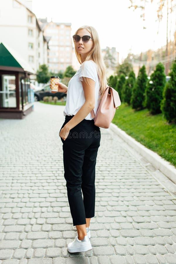 Retrato de uma jovem mulher fora e guardando uma xícara de café imagens de stock