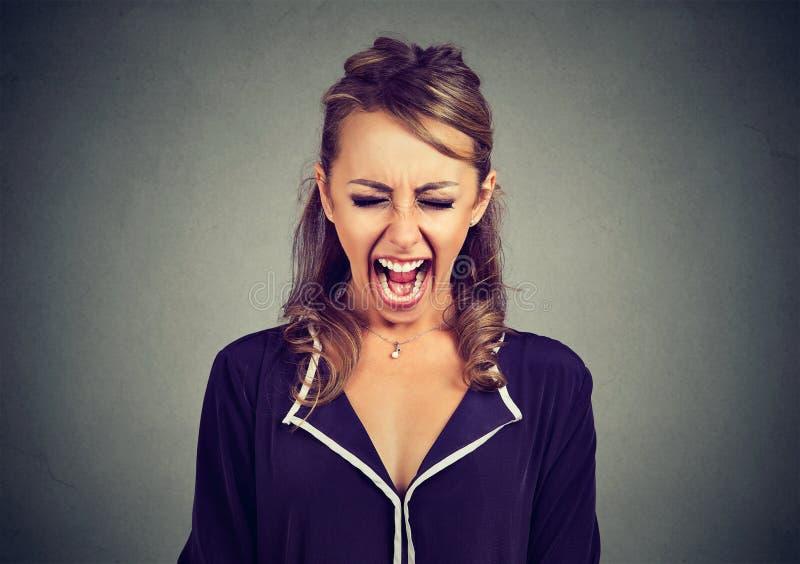 Retrato de uma jovem mulher frustrante irritada que grita fotos de stock royalty free