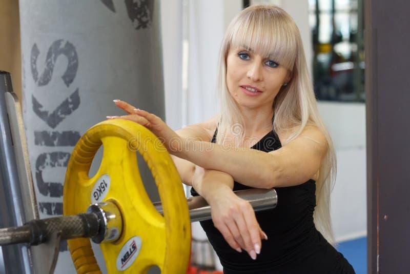 Retrato de uma jovem mulher louro que inclina-se na barra do barbell e que prepara-se para começar exercitar imagens de stock