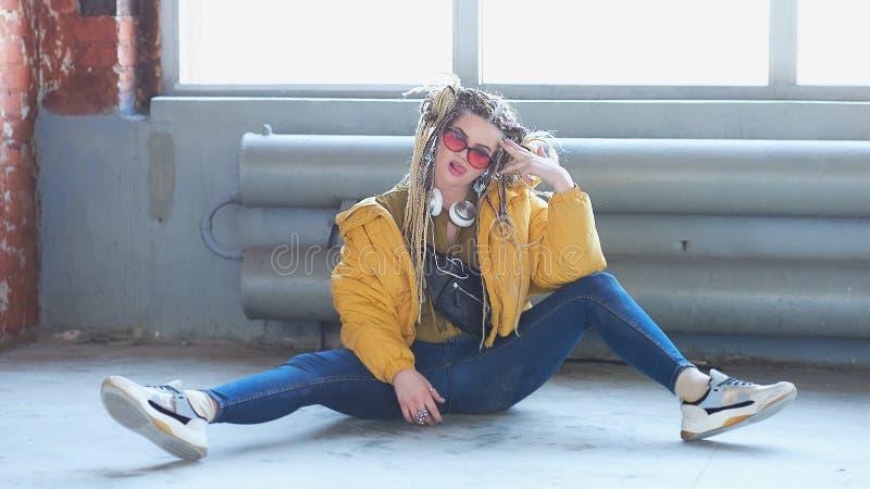 Retrato de uma jovem mulher moderna excêntrica, de uns óculos de sol brilhantes da composição, e de um penteado louco ¼ de Ð fotografia de stock