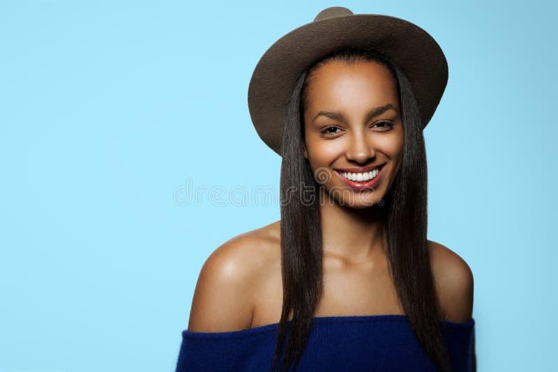 Retrato de uma jovem mulher moreno toothy, vestido no chapéu do brrown e nos ombros despidos, isolados em um fundo azul fotos de stock royalty free