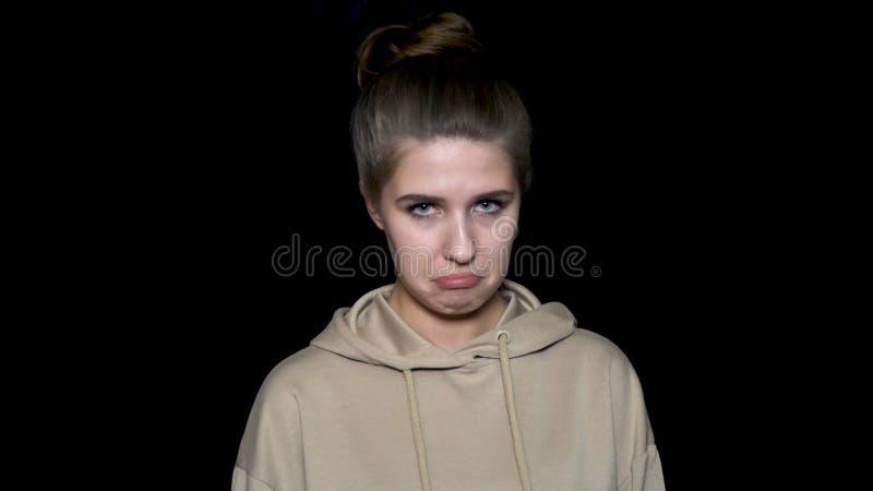 Retrato de uma jovem mulher muito triste e deprimida isolada no fundo preto Mulher muito triste, infeliz com criançola fotos de stock royalty free