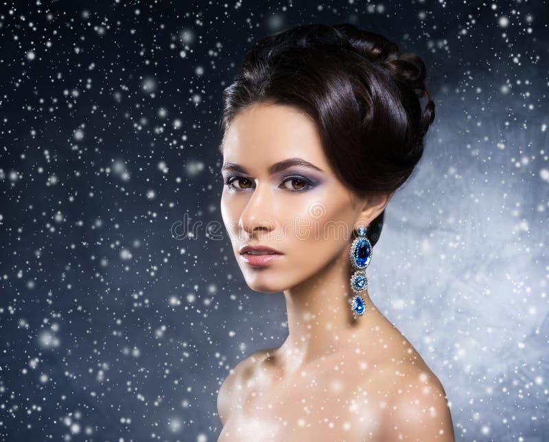 Retrato de uma jovem mulher na joia na neve imagens de stock