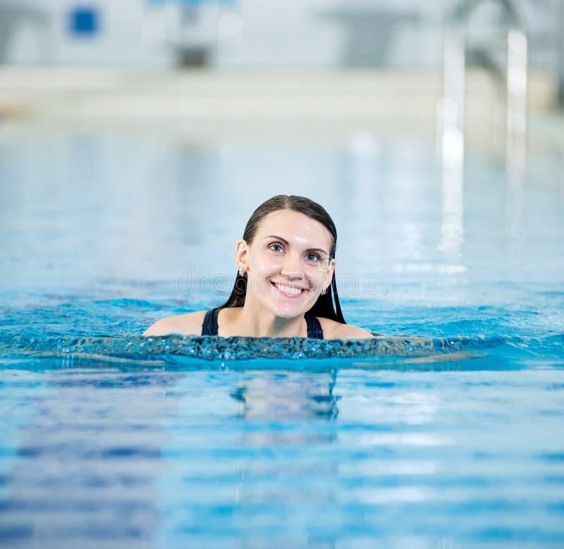 Retrato de uma jovem mulher na piscina do esporte fotos de stock