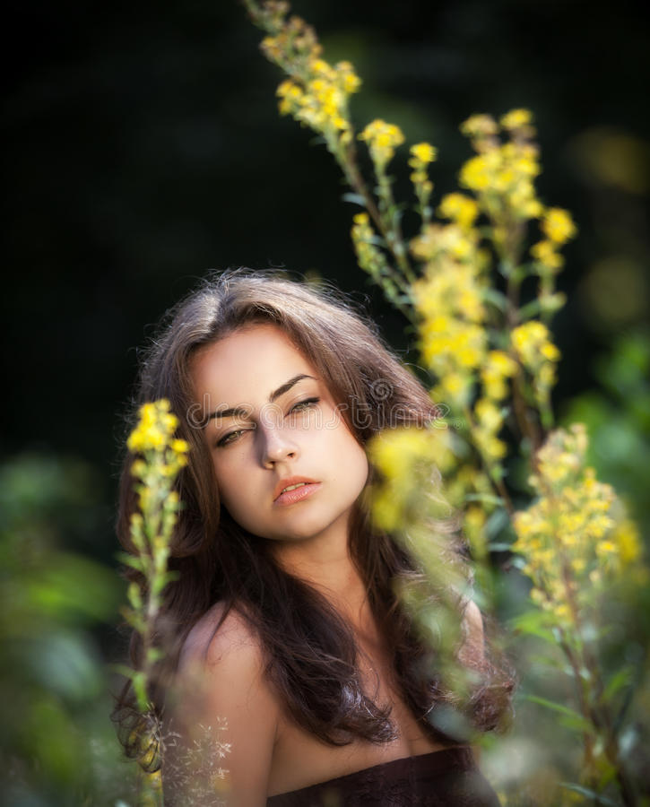 Retrato de uma jovem mulher nas flores fotografia de stock royalty free