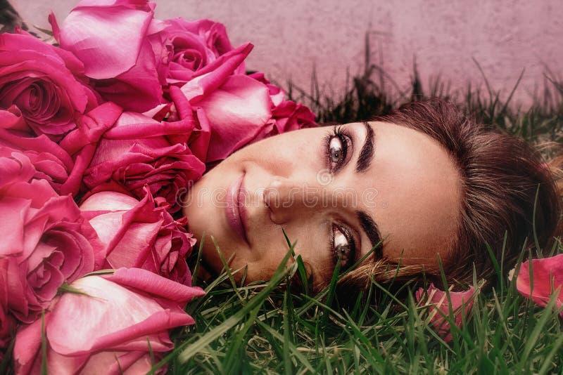 Retrato de uma jovem mulher nas rosas na grama Retrato da arte fotos de stock royalty free