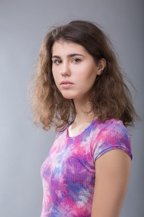 Retrato de uma jovem mulher ordinária no fundo cinzento fotos de stock royalty free