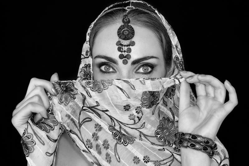 Retrato de uma jovem mulher oriental em um lenço com um ornamento e as joias em preto e branco fotografia de stock