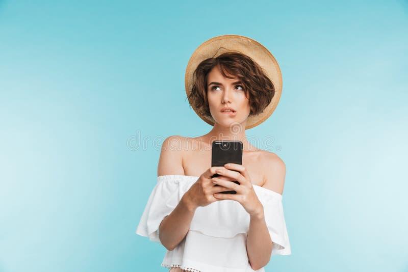 Retrato de uma jovem mulher pensativa no chapéu do verão imagem de stock