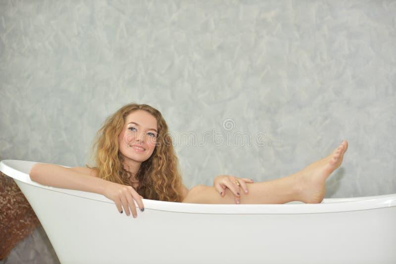 Retrato de uma jovem mulher que coloca na banheira tempo relaxado no banheiro imagem de stock