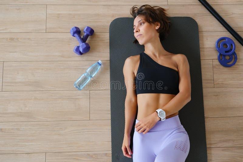 Retrato de uma jovem mulher que descansa na esteira da ioga no gym foto de stock royalty free