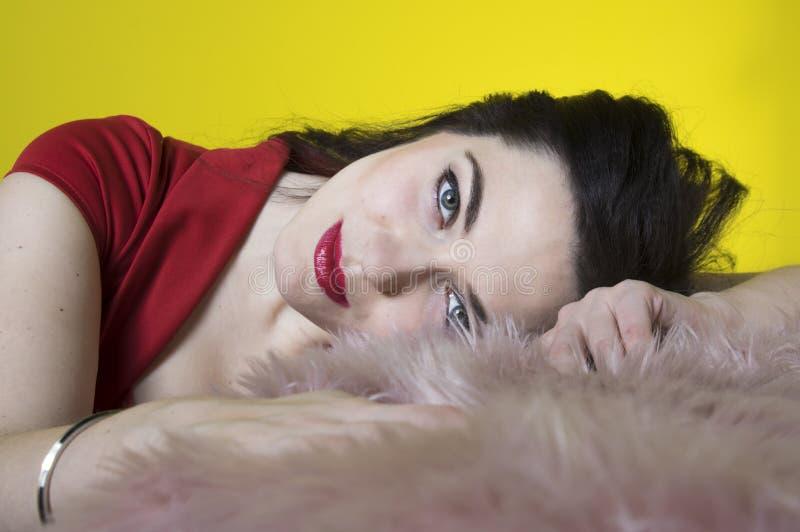 Retrato de uma jovem mulher que encontra-se na pele artificial A morena bonita toca na pele com seus mãos e olhares fixos em você fotografia de stock