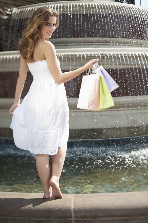 Retrato de uma jovem mulher que está por sacos de compras levando da fonte foto de stock royalty free