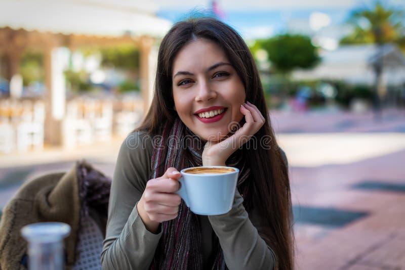 Retrato de uma jovem mulher que guarda um copo de café fotos de stock royalty free