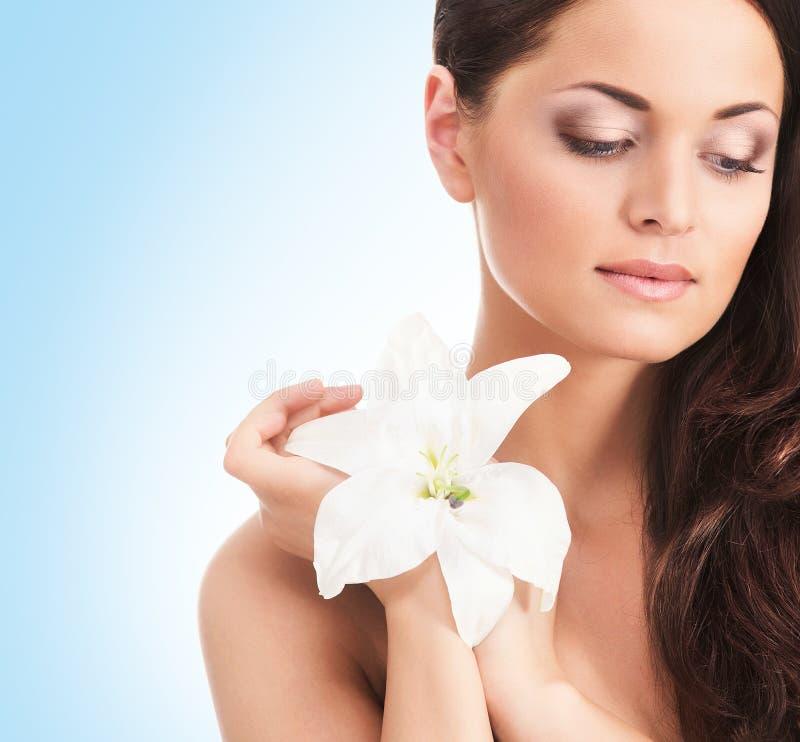 Retrato de uma jovem mulher que guarda uma flor do whit foto de stock royalty free