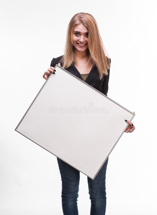 Retrato de uma jovem mulher que guardara o quadro de avisos vazio fotografia de stock