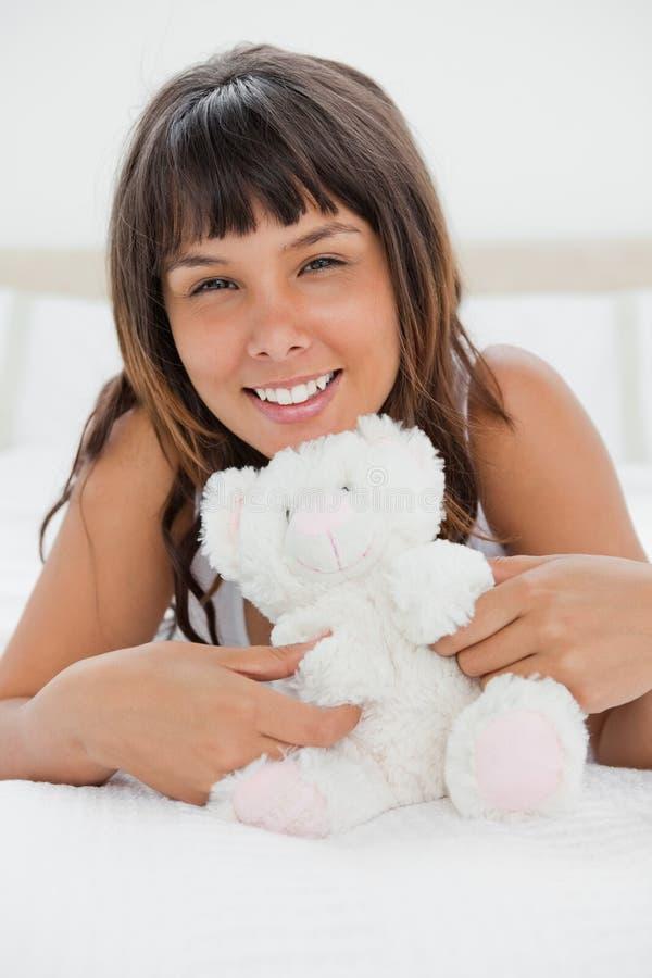Retrato de uma jovem mulher que joga com um urso de peluche imagem de stock