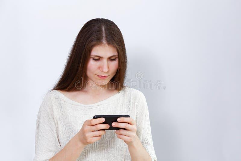 Retrato de uma jovem mulher que joga um jogo ou que olha um filme no smartphone imagem de stock royalty free