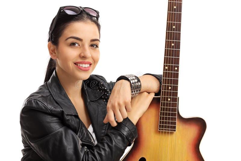 Retrato de uma jovem mulher que levanta com uma guitarra foto de stock