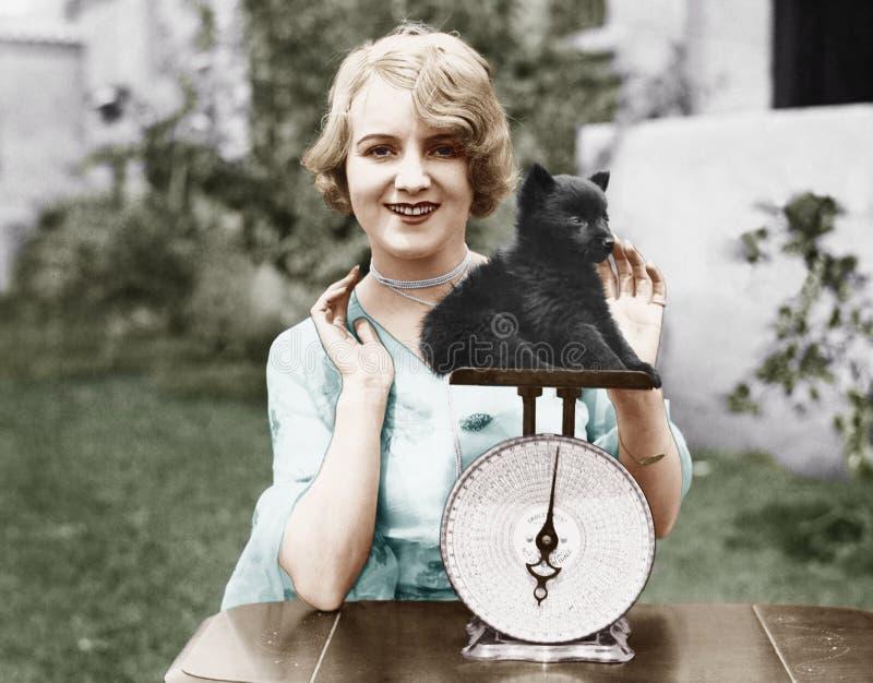 Retrato de uma jovem mulher que pesa seu cachorrinho em uma escala de peso (todas as pessoas descritas não são umas vivas mais lo imagens de stock royalty free