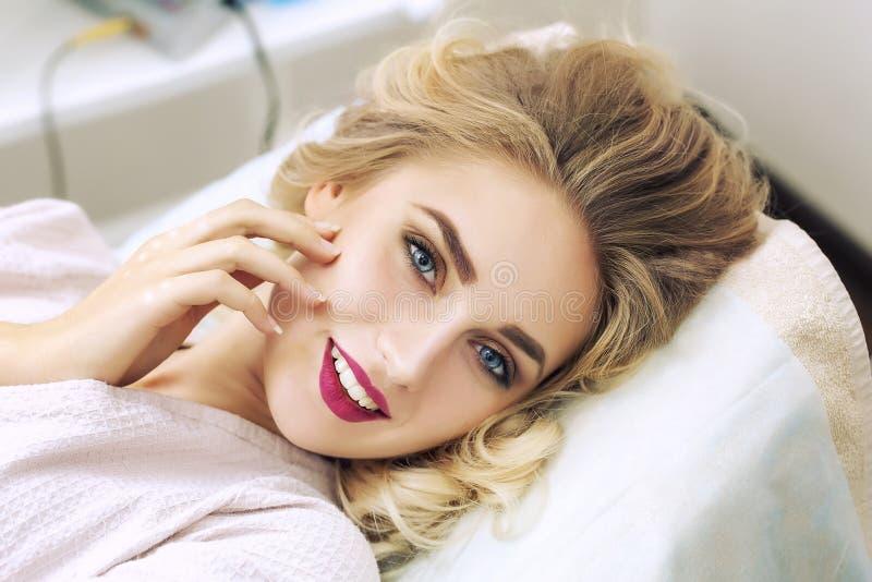 Retrato de uma jovem mulher que relaxa nos termas no roupão fotografia de stock royalty free