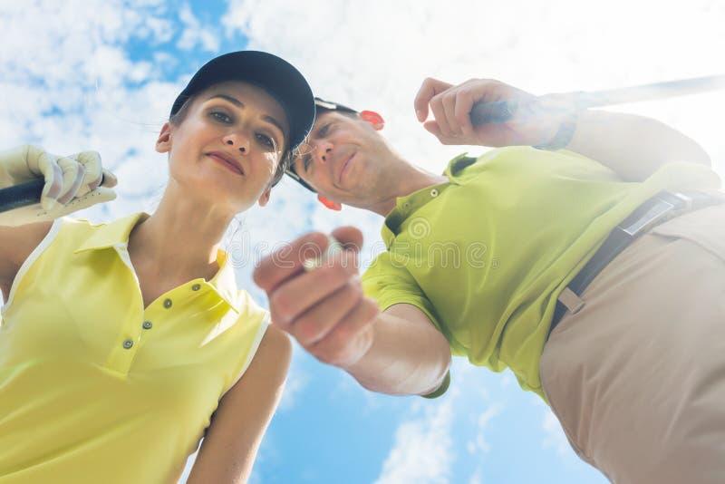 Retrato de uma jovem mulher que sorri durante o jogo de golfe profissional fotos de stock