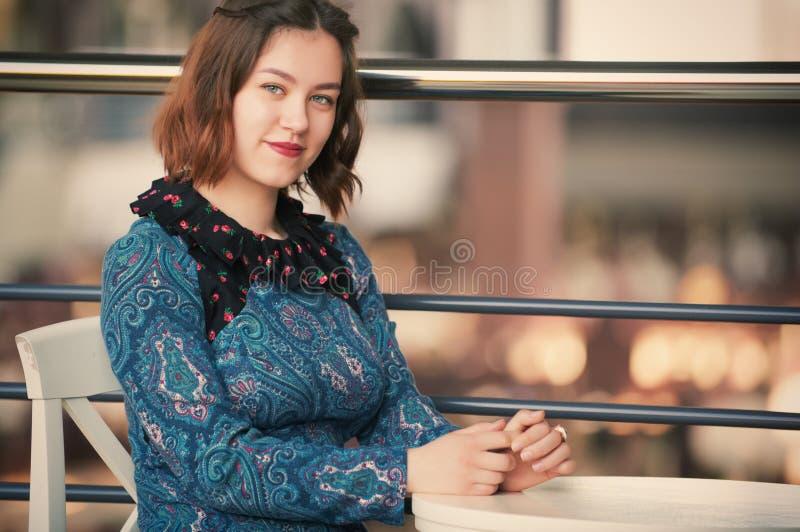 Retrato de uma jovem mulher de sorriso que senta-se no café imagem de stock