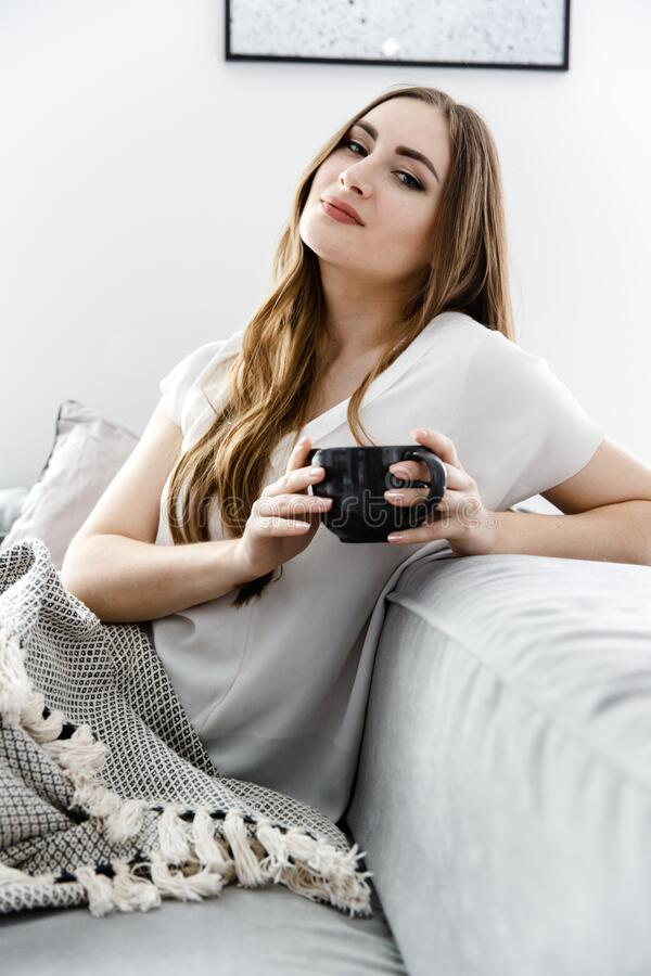 Retrato de uma jovem que bebe chá debaixo das capas do sofá e olha para a câmera fotografia de stock