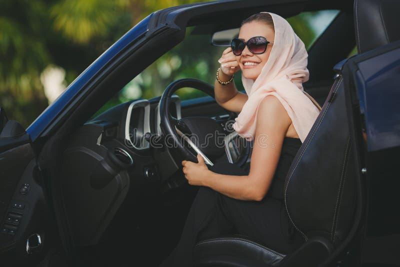 Retrato de uma jovem senhora em um convertible preto fotografia de stock