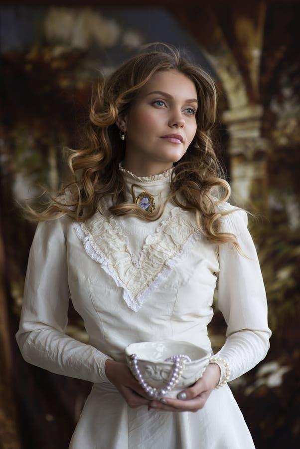 Retrato de uma jovem senhora em um vestido branco do vintage foto de stock royalty free