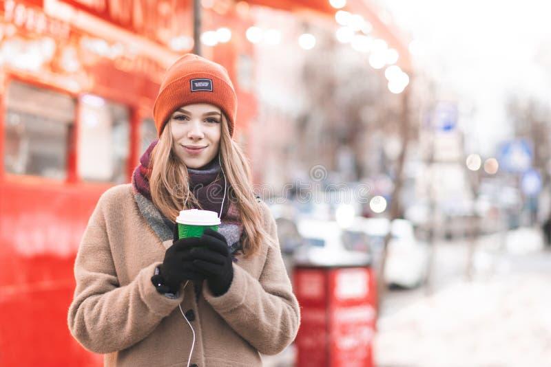 Retrato de uma jovem senhora na roupa e em fones de ouvido mornos, estando no fundo da rua, xícara de café de papel nela fotografia de stock royalty free