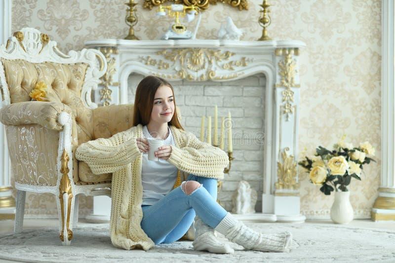 Retrato de uma linda adolescente com xícara de chá sentada no chão foto de stock royalty free