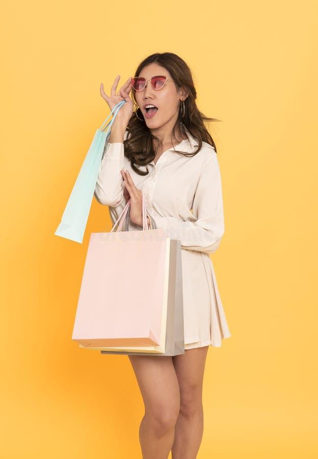 Retrato de uma linda garota asiática excitada usando vestido e óculos escuros segurando sacos de compras isolados sobre fundo ama imagens de stock