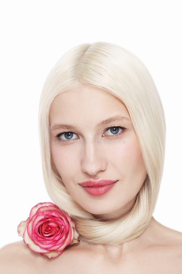 Retrato de uma linda loira com maquiagem limpa e rosa rosa imagens de stock royalty free
