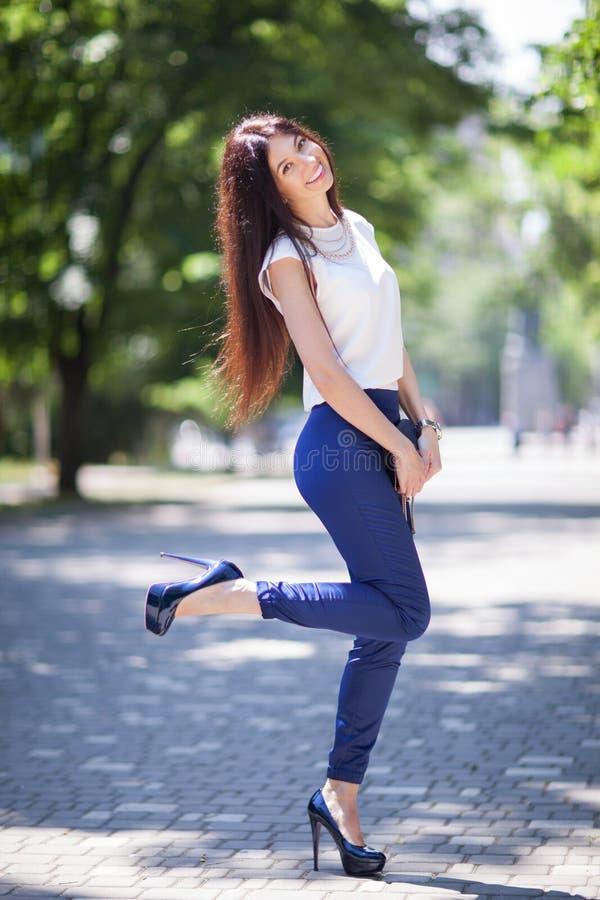 Retrato de uma linda mulher feliz e elegante com cabelo comprido em sapatos de salto alto, caminhando no parque urbano Estilo de  fotografia de stock