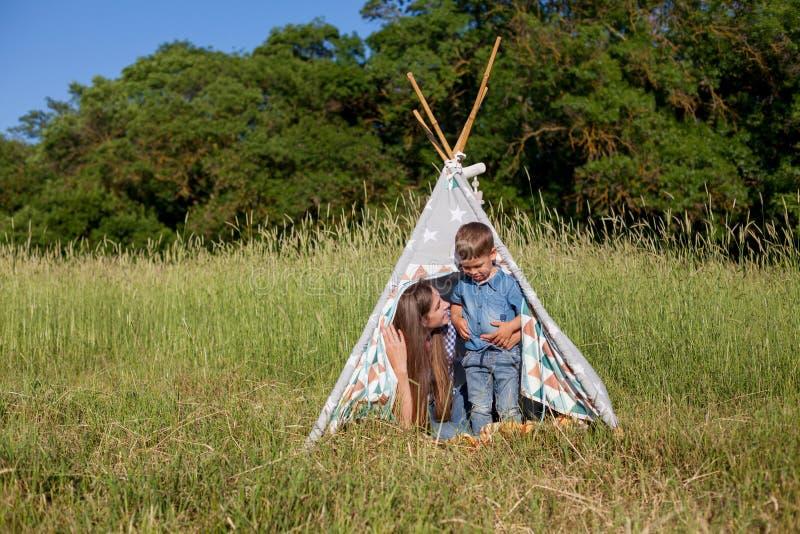 Retrato de uma mãe com um filho novo para comer em um piquenique na floresta fotografia de stock royalty free
