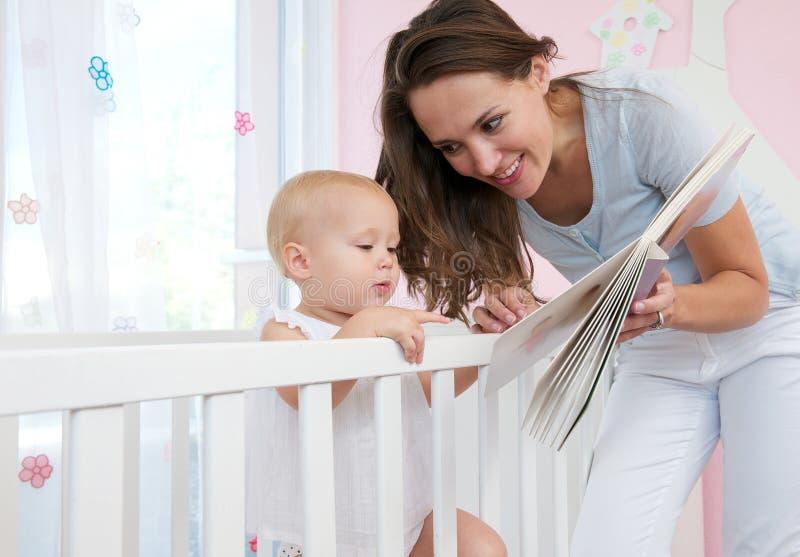 Retrato de uma mãe e de uma criança que leem um livro junto imagens de stock