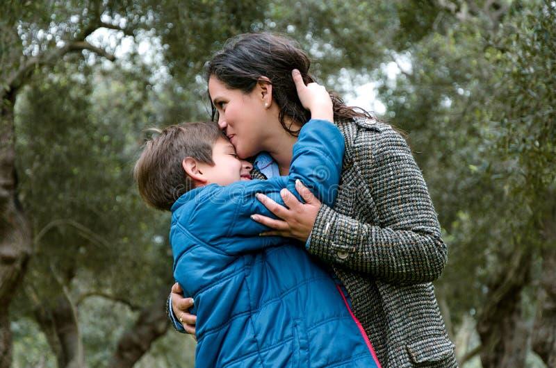 Retrato de uma mãe que beija seu filho pequeno no parque fotografia de stock royalty free