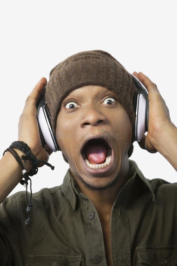 Retrato de uma música de escuta surpreendida do homem afro-americano novo através dos auscultadores fotografia de stock royalty free