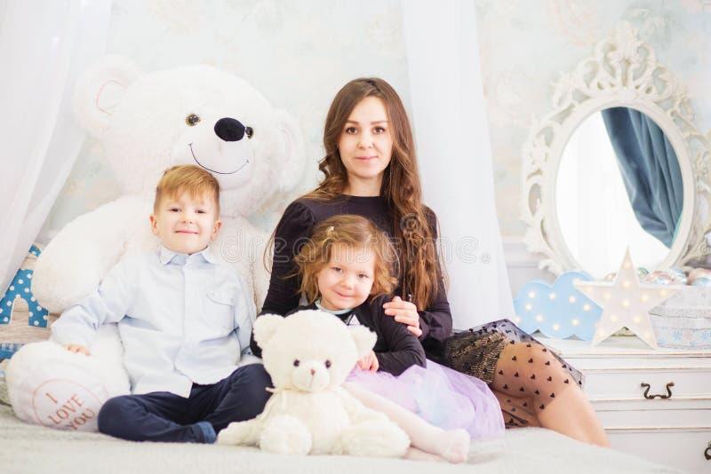 Retrato de uma m?e feliz e de suas duas crian?as pequenas - menino e menina Retrato feliz da fam?lia Crian?as com brinquedos fotos de stock royalty free