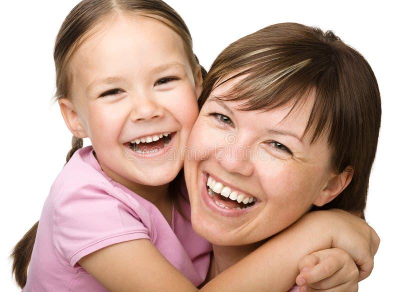 Retrato de uma matriz feliz que abraça sua filha fotos de stock