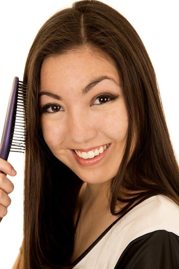 Retrato de uma menina adolescente asiática nova bonito que escova seu cabelo imagem de stock royalty free