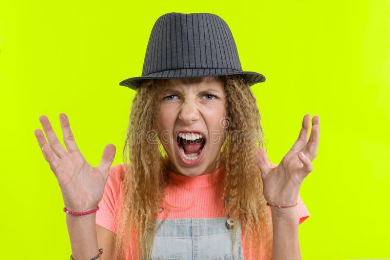 Retrato de uma menina adolescente gritando agressiva sobre o fundo amarelo do estúdio fotos de stock royalty free
