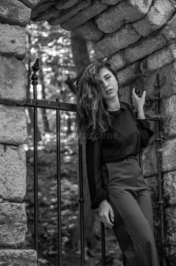Retrato de uma menina adolescente nova e atrativa bonita com cabelo longo perto das portas de aço do castelo de pedra destruído e fotografia de stock royalty free