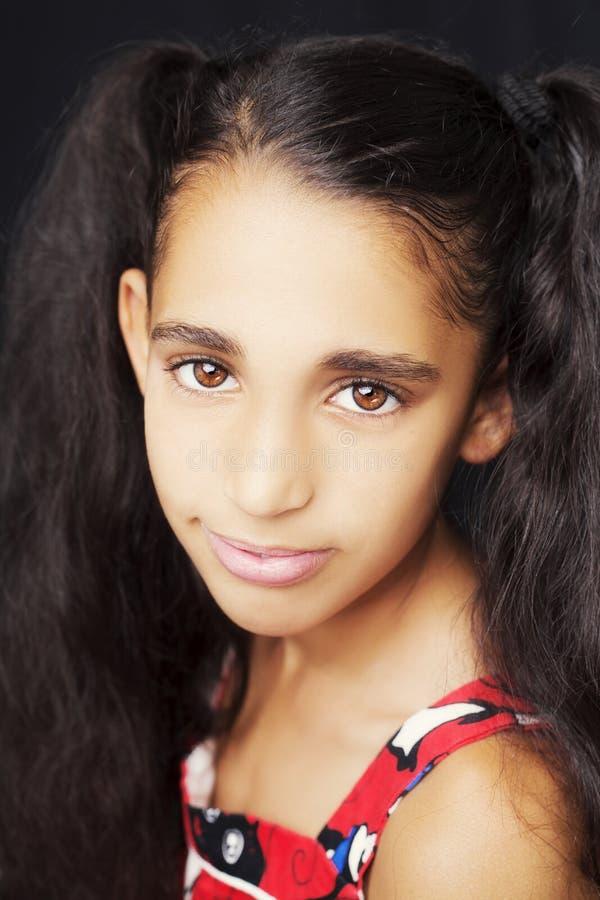 Retrato de uma menina africana bonita no fundo preto fotografia de stock