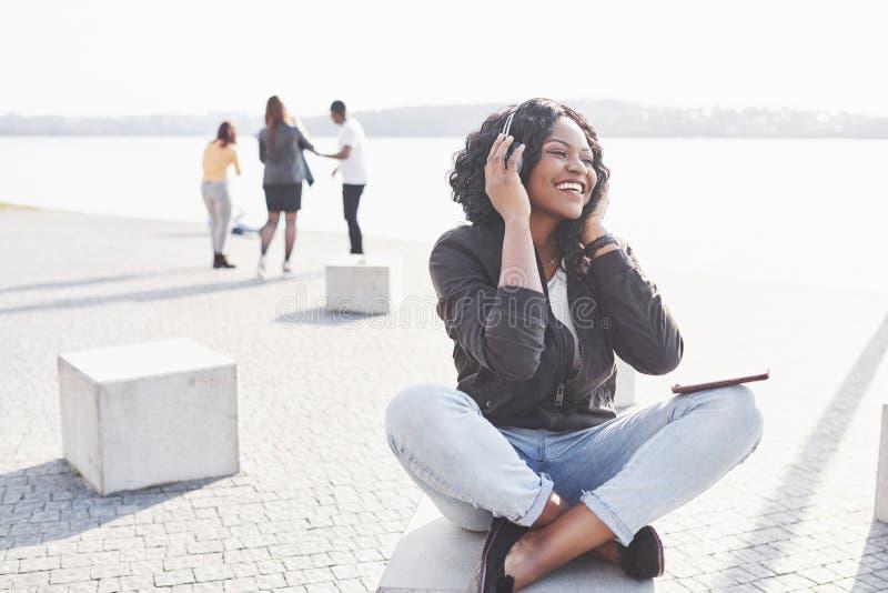Retrato de uma menina afro-americano bonita nova bonita que senta-se na praia ou no lago e que escuta a música nela imagens de stock
