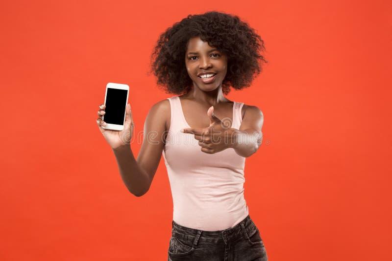 Retrato de uma menina afro ocasional segura que mostra o telefone celular da tela vazia isolado sobre o fundo vermelho fotos de stock royalty free