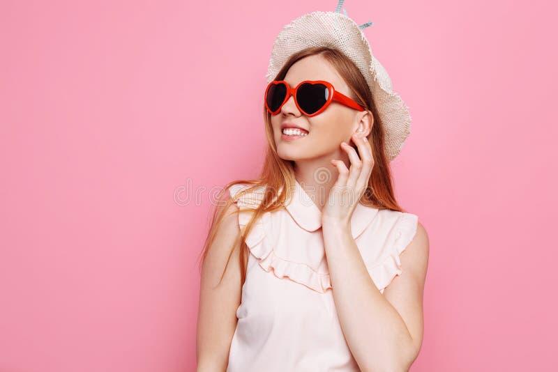 Retrato de uma menina alegre em um chapéu do verão e em uns óculos de sol coração-dados forma que esperam umas férias fotografia de stock royalty free
