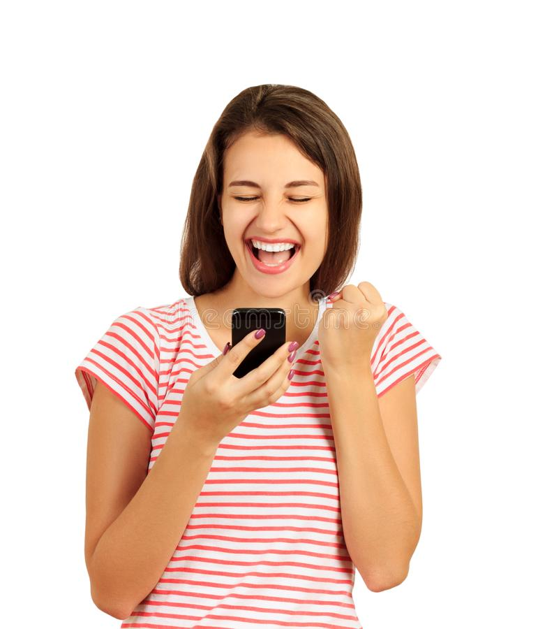 Retrato de uma menina alegre feliz que guarda o telefone celular e que comemora uma vitória menina emocional isolada no fundo bra imagens de stock