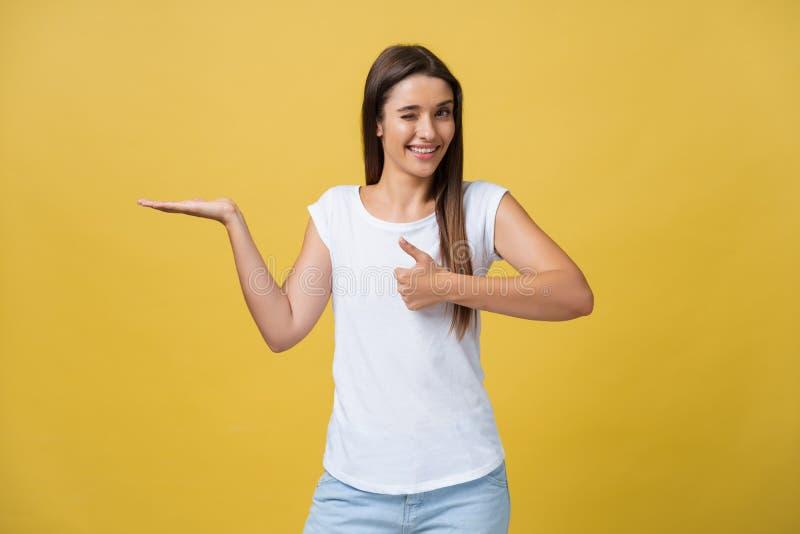 Retrato de uma menina alegre que guarda o copyspace na palma isolada em um fundo amarelo fotografia de stock royalty free